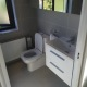This beautiful grey bathroom features close coupled back to wall pan and cistern, white wall hung basin unit, modern grey tiles, single ended bath and an electric shower.