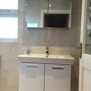 Bathroom design featuring mosaics tiles & grey tiles, walk in shower, wall hung basin unit, mirrored cabinet and back to wall pan cistern - by Cleary Bathroom Design