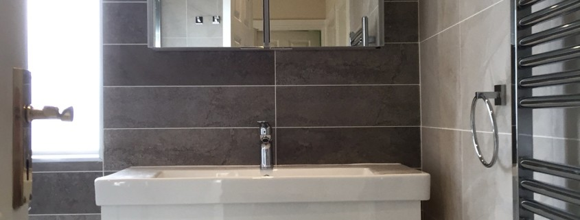 This cluttered family bathroom was refurbished by Cleary Bathroom Design, Bathroom storage, low profile tray, and grey tiles for a sleek minimal look!