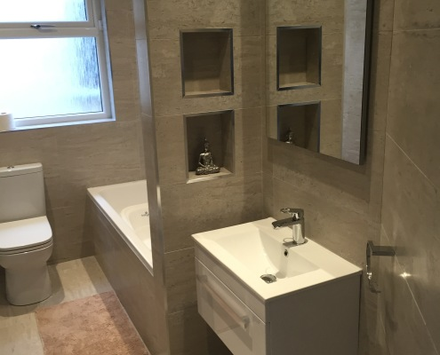 main bathroom features a recess shelf in shower area and above unit, wall hung basin unit, close coupled back to wall toilet, and gorgeous wood effect floor tiles and grey / beige wall tiles for a timeless look.