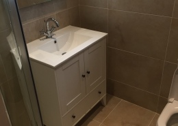This bathroom makeover features a slim shower tray, warm beige wall and floor tiles, floor standing basin unit, basin mixer tap and Led mirror.