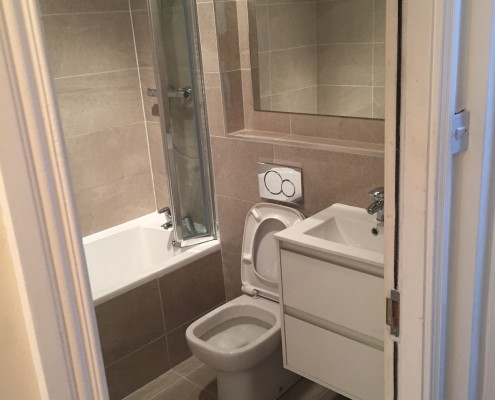 Main Bathroom Renovation - Ringsend This dated white bathroom is now a neutral, warm, timeless bathroom. Featuring close coupled back to wall toilet, wall hung basin unit, basin mixer, bespoke mirror, single ended bath with shower valve. Completed 8/07/16