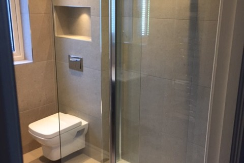 "This main bathroom design features a wall hung unit and toilet, low profile shower tray, two recess shelves above toilet with Led lighting, Chrome heated towel rad with ""Aromawell"" a specially crafted well within the radiator which holds aromatherapy oil and gently releases the scent when the heating is on."
